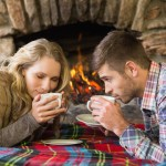 Side view of a romantic young couple drinking tea in front of lit fireplace